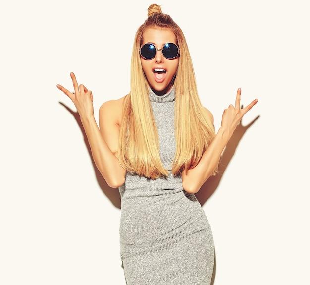 アヒルの顔を作るとピースサインを示す白で隔離されるメイクなしのカジュアルなヒップスターグレー夏服で美しい金髪の女性