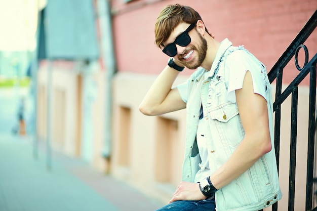 サングラスの通りにスタイリッシュな夏布で面白い笑顔ヒップスターハンサムな男男