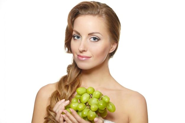白で隔離される長い髪と彼女の手でブドウの房を保持している若いセクシーな笑顔美人