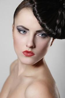 Портрет красивой молодой женщины с красными губами и необычной прической на сером