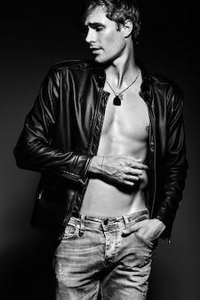 若いハンサムな筋肉フィットレザージャケットで彼の腹部の筋肉を示すスタジオでポーズをとる男性モデル男