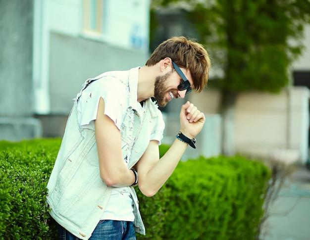 サングラスの通りにスタイリッシュな布で面白い笑顔ヒップスターハンサムな男男