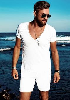 Портрет красавец модной модели носить белые одежды позирует на синем море