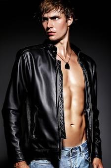 Молодой красивый мускулистый мужчина модель позирует в студии, показывая его мышцы живота в кожаной куртке