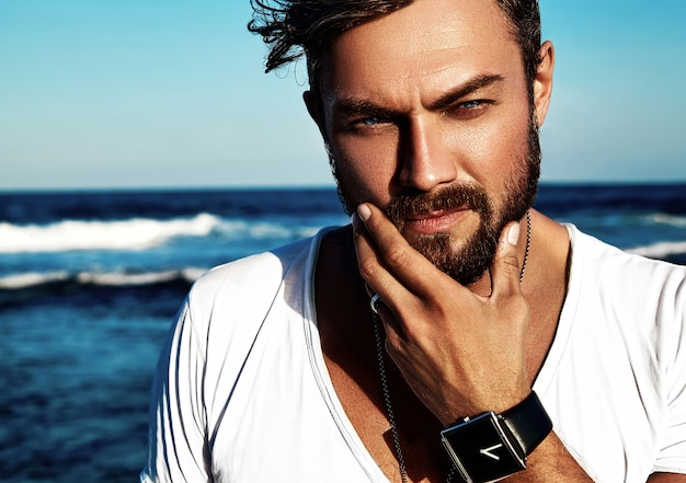 青い海でポーズをとって白い服を着ているハンサムなファッション男モデルの肖像