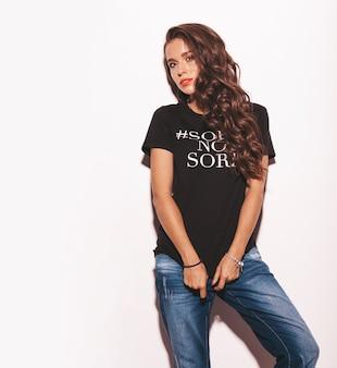 Молодая красивая женщина в модной летней черной футболке и джинсовой одежде.