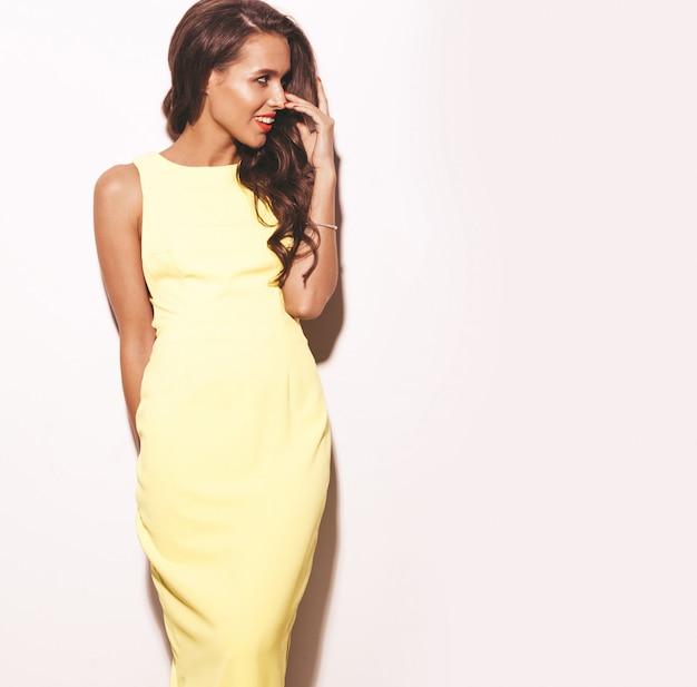 白で隔離される夏の明るい黄色のドレスに赤い唇とファッショングラマースタイリッシュな美しい若い女性モデル