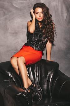 Молодая красивая женщина в модной летней красной юбке и черной кожаной куртке.
