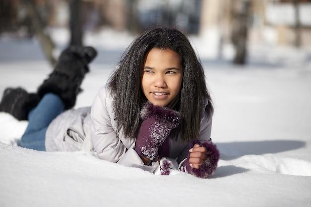 屋外の雪の中で横になっている美しい笑顔アメリカ黒人女性