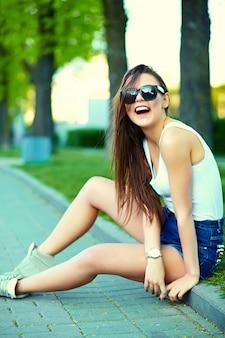 通りの夏の明るい布でグラマースタイリッシュな女性モデル