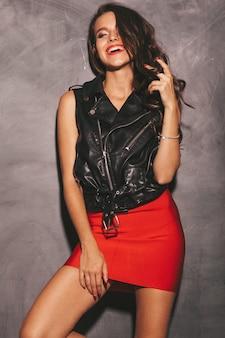 Молодая красивая улыбающаяся женщина в модной летней красной юбке и черной кожаной куртке.