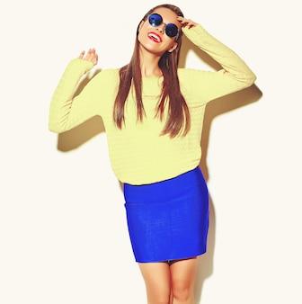 Портрет красивой счастливой милой улыбающейся брюнетки девушки в повседневной красочной хипстерской желтой летней одежде с красными губами на белом