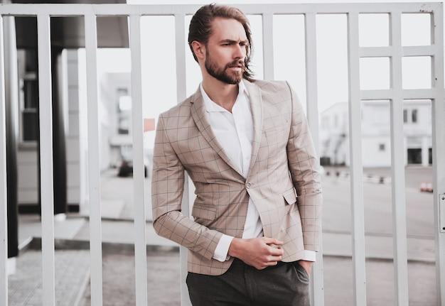 Портрет сексуальный красивый модный мужской модель мужчина одет в элегантный бежевый клетчатый костюм позирует на фоне улицы