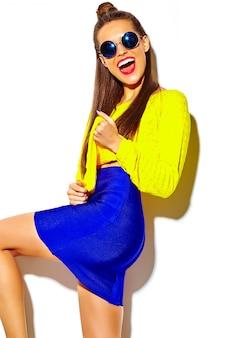 白で隔離される赤い唇とカジュアルなカラフルな黄色の夏服に夢中になって流行に敏感な女の子を笑顔陽気なファッションの肖像画