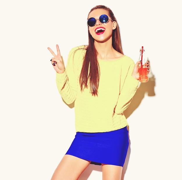 Портрет красивой сумасшедшей улыбающейся брюнетки девушки в повседневной хипстерской летней красочной одежде с красными губами