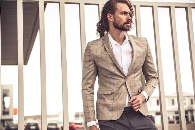 Портрет сексуальный красивый модный бизнесмен модель, одетый в элегантный клетчатый костюм