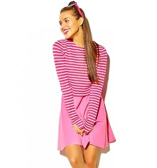 Портрет красивой счастливой милой улыбающейся брюнетки девушки в повседневной красочной хипстерской летней розовой одежде с красными губами на белом