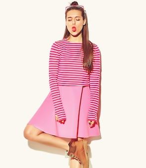 赤い唇とカジュアルなカラフルなヒップスター夏ピンクの服で美しい幸せなかわいい笑顔ブルネットの女性少女