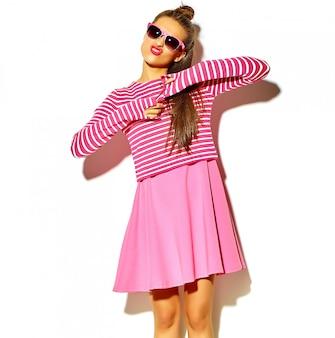 アヒルの顔を作る白で隔離される赤い唇とカジュアルなカラフルなヒップスター夏ピンクの服で美しい幸せなかわいい笑顔ブルネットの女性少女