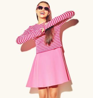 Красивая счастливая милая улыбающаяся брюнетка женщина девушка в повседневной красочной хипстерской летней розовой одежде с красными губами на белом в темных очках