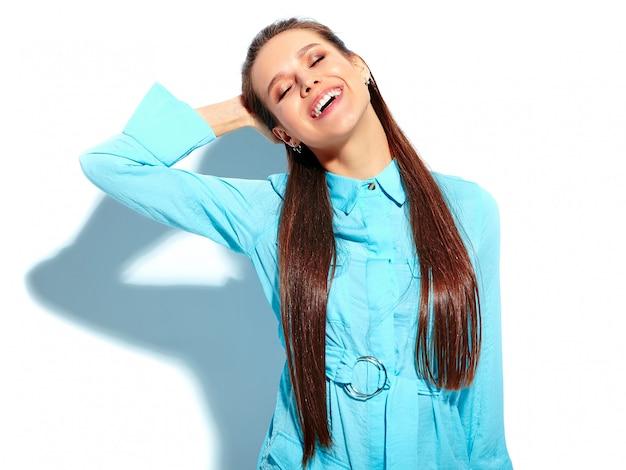 白い背景に分離された明るい青い夏スタイリッシュなドレスで美しい白人笑顔ブルネットの女性モデル