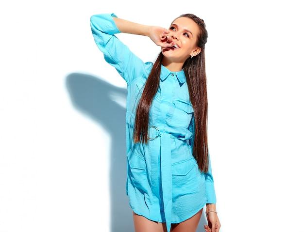 白い背景に分離された明るい青い夏スタイリッシュなドレスで美しい白人笑顔ブルネットの女性モデル。彼女の指をかむ