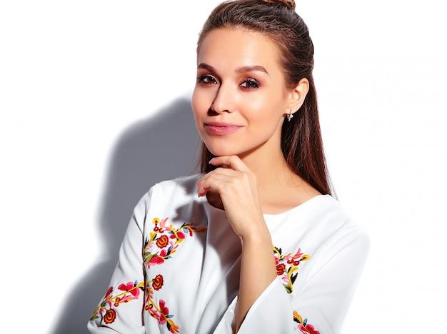 Портрет красивой кавказской улыбающейся брюнетки модели в белом летнем стильном платье на белом фоне