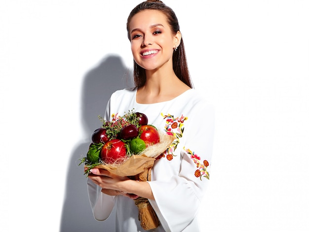 花の珍しい創造的な花束と白い夏のスタイリッシュなドレスで美しい白人笑顔ブルネットの女性モデルの肖像画
