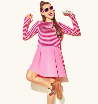 赤い唇とカジュアルなカラフルなピンクの夏服で美しい幸せなかわいい笑顔セクシーなブルネットの女性少女を踊る