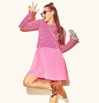 カジュアルなカラフルなピンクの夏服で美しい幸せなかわいい笑顔セクシーなブルネットの女性少女を踊る