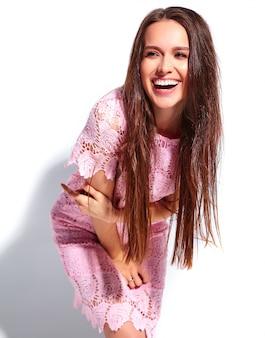 Портрет красивой кавказской улыбающейся брюнетки модели в ярко-розовом летнем стильном платье на белом фоне
