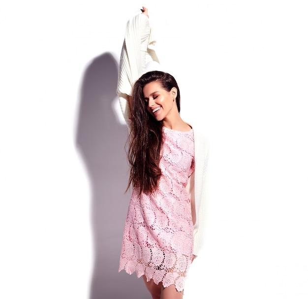 白い背景に分離された明るいピンク夏スタイリッシュなドレスで美しい白人笑顔ブルネットの女性モデルの肖像画。祝う