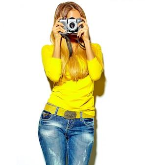 カジュアルな夏服で美しい幸せなかわいい笑顔金髪女性少女の肖像画は、レトロな写真用カメラを保持している写真を撮る
