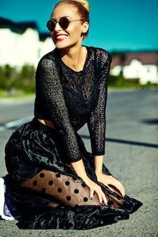 通りに座って夏黒ヒップスター服で面白いスタイリッシュなセクシーな笑顔美しい若いブロンドの女性モデル