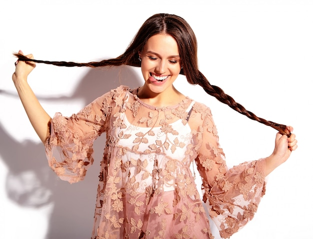 Портрет красивой кавказской усмехаясь модели женщины брюнет в одеждах яркого розового лета стильных изолированных на белой предпосылке.