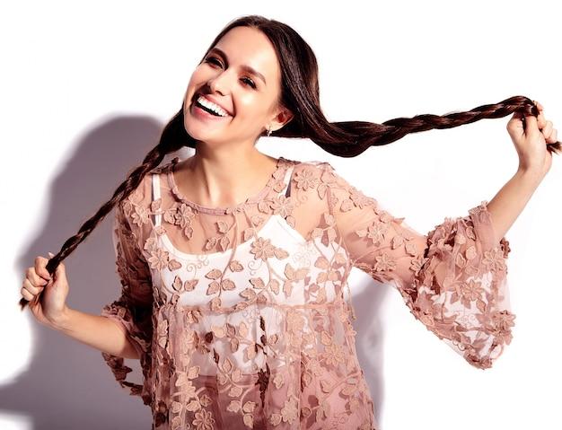 白い背景に分離された明るいピンク夏スタイリッシュな服で美しい白人笑顔ブルネットの女性モデルの肖像画。