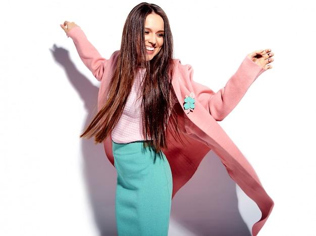 Портрет красивой кавказской улыбающейся брюнетки модели в ярко-розовом пальто и летней стильной синей юбке на белом фоне
