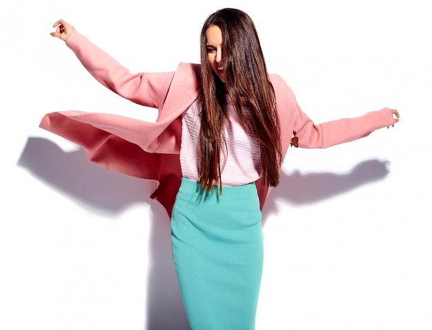Портрет красивой кавказской улыбающейся брюнетки модели в ярко-розовом пальто и летней стильной синей юбке