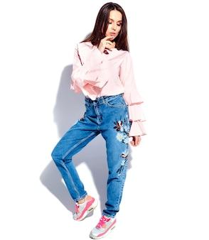 Портрет красивой кавказской улыбающейся брюнетки модели в ярко-розовой блузке и летних стильных синих джинсах с цветочным принтом
