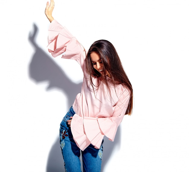 Портрет красивой кавказской улыбающейся брюнетки модели в ярко-розовой блузке и стильных летних синих джинсах