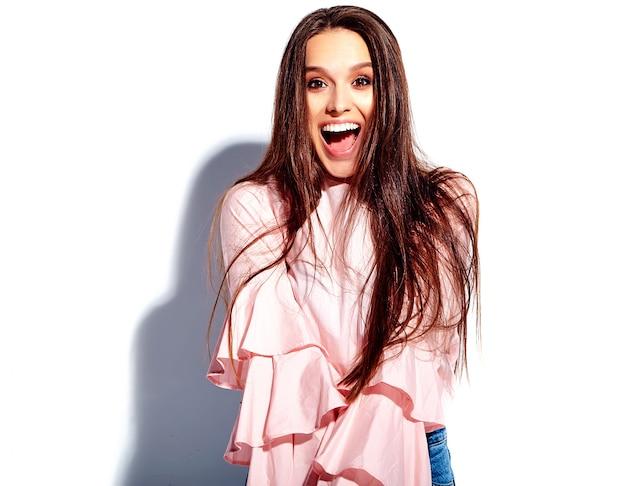 Портрет красивой кавказской улыбающейся брюнетки модели в ярко-розовой блузке и летних стильных синих джинсах с цветами