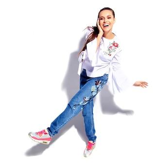 Портрет красивой кавказской улыбающейся брюнетки модели в белой блузке и летних стильных синих джинсах с цветами