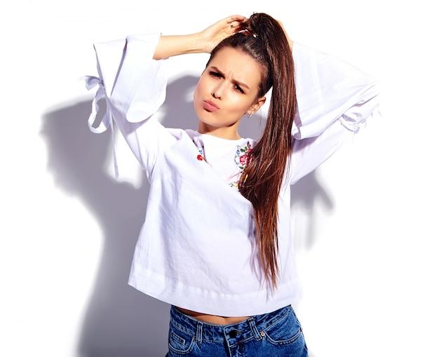 Портрет красивой кавказской улыбающейся брюнетки модели в белой блузке и летних стильных синих джинсах с цветочным принтом