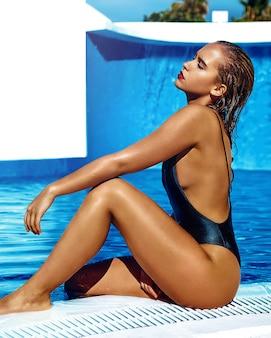 Красивая девушка модель с темными волосами в черном купальнике