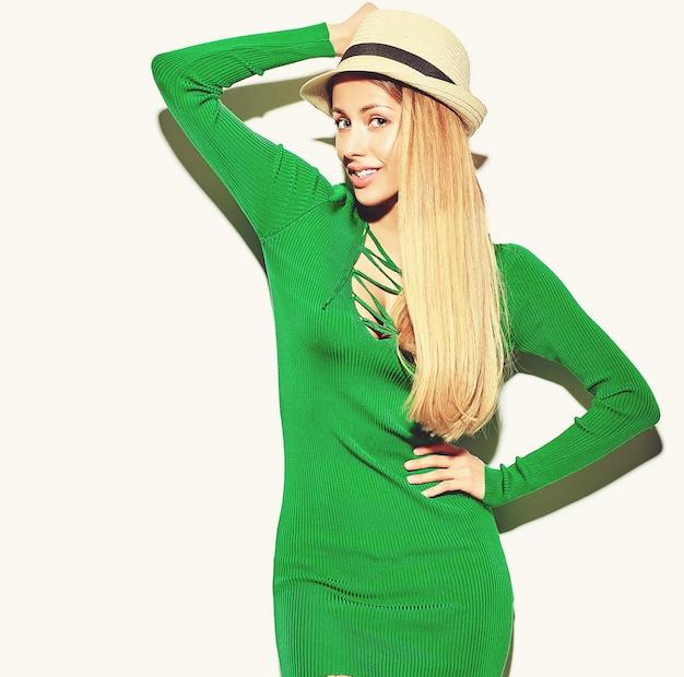 Красивая счастливая милая усмехаясь белокурая девушка девушки в вскользь одеждах зеленого цвета битника лета без состава изолированная на белизне с шляпой