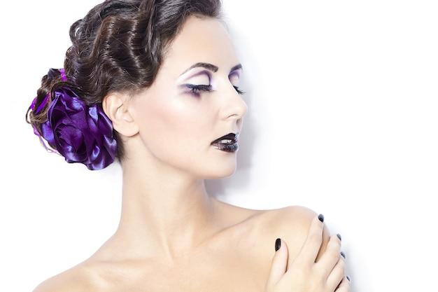 美容と健康、化粧品、化粧。明るい紫色の化粧、明るい白い背景に巻き毛のヘアスタイルとファッション女性モデルの肖像画。