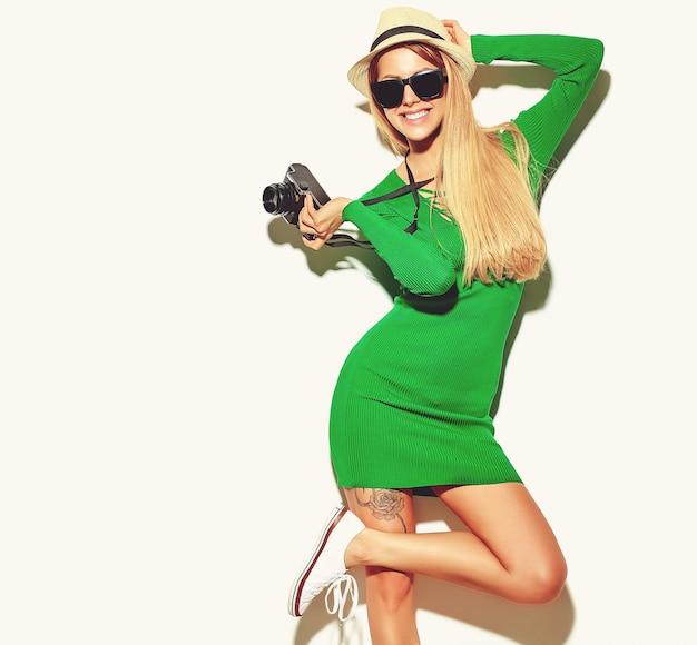 Красивая счастливая милая белокурая женщина девушка в повседневной летней одежде зеленого битника снимает фото с ретро фотоаппаратом