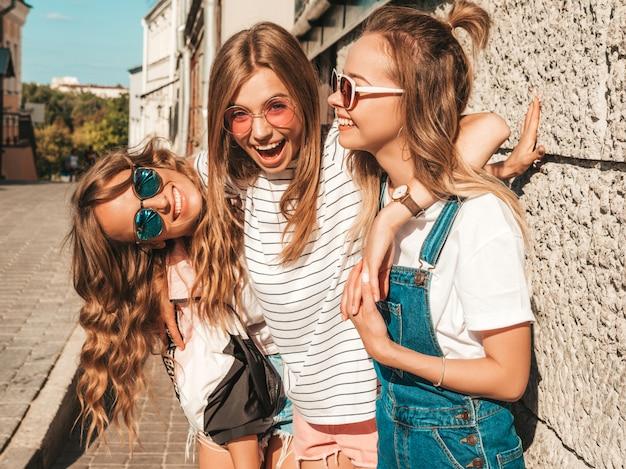 Портрет сексуальных беззаботных женщин, позирует на улице возле стены. позитивные модели, с удовольствием в солнцезащитные очки.