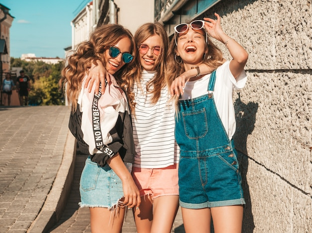 Портрет сексуальных беззаботных женщин, создавая на фоне улицы. позитивные модели, с удовольствием в солнцезащитные очки.