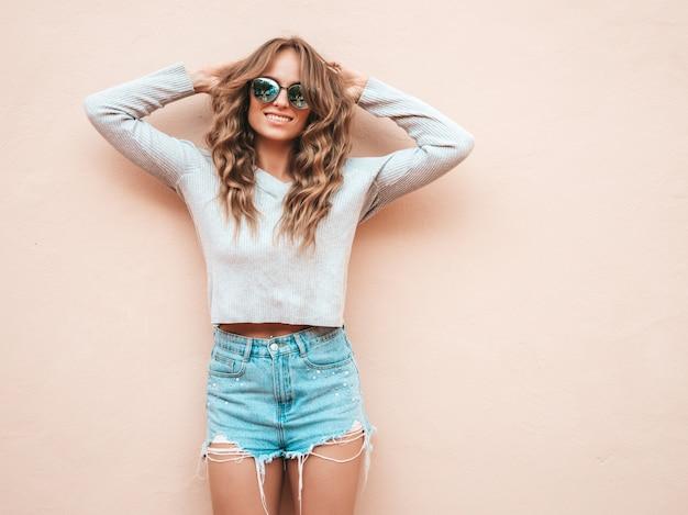 夏の流行に敏感なジーンズのショートパンツの服に身を包んだ美しい笑顔モデルの肖像